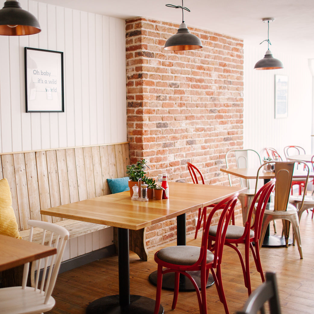 hanging light in cafe with red chairs and brick wall