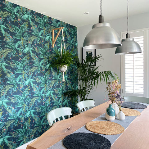 A dining room with leaf-patterned wallpaper, woven placemats and macramé baskets