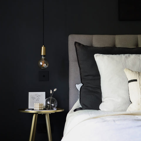 A bedroom with black walls, white bedding and a hanging light