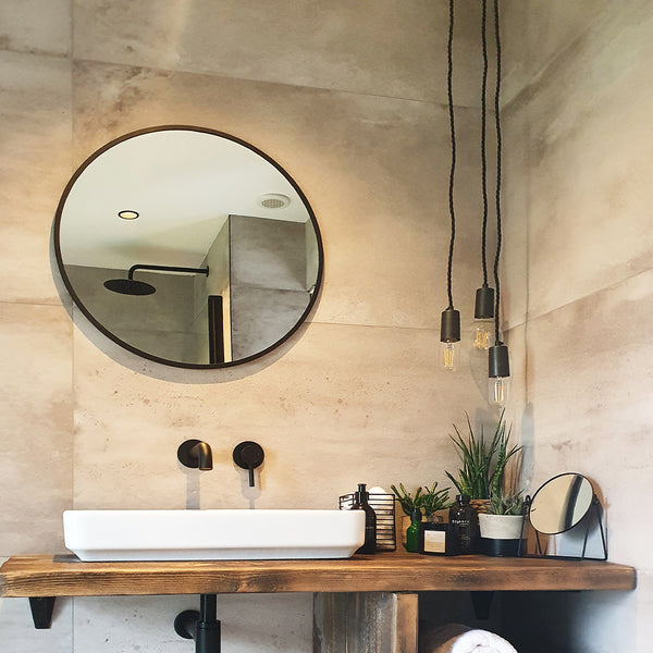 An industrial-style bathroom with hanging lights by Industville
