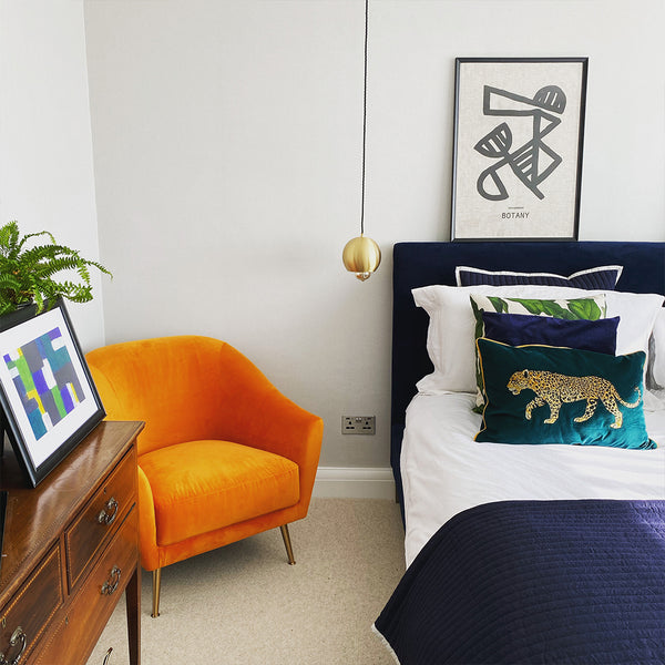 A colourful bedroom with prints and metal hanging side light