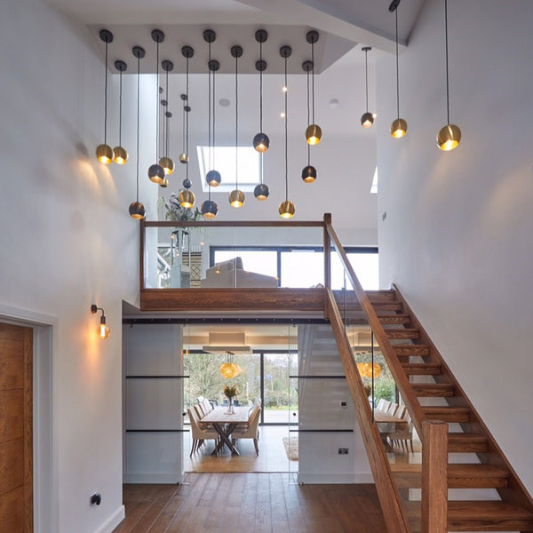 A modern open home reception with hanging industrial lighting