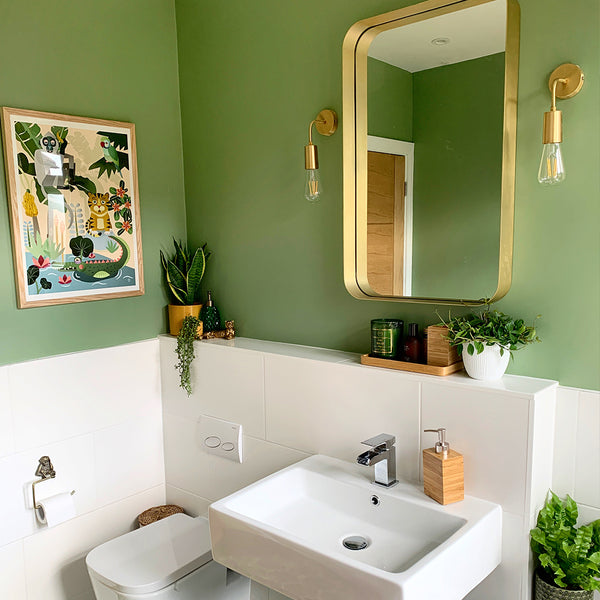 A green bathroom with brass features