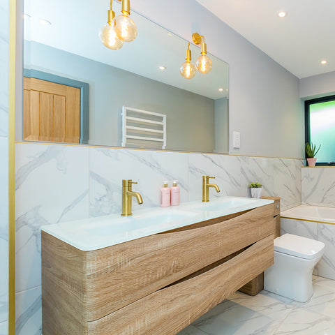 marble effect bathroom with light wood furniture