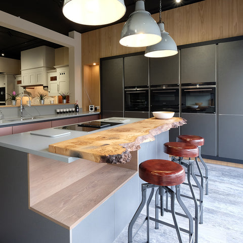 A modern kitchen with rustic wooden counter and leather stools by Industville