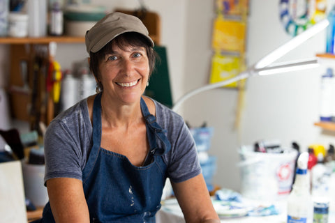 Ruth Fromstein, an artist in her studio surrounded by paint and works