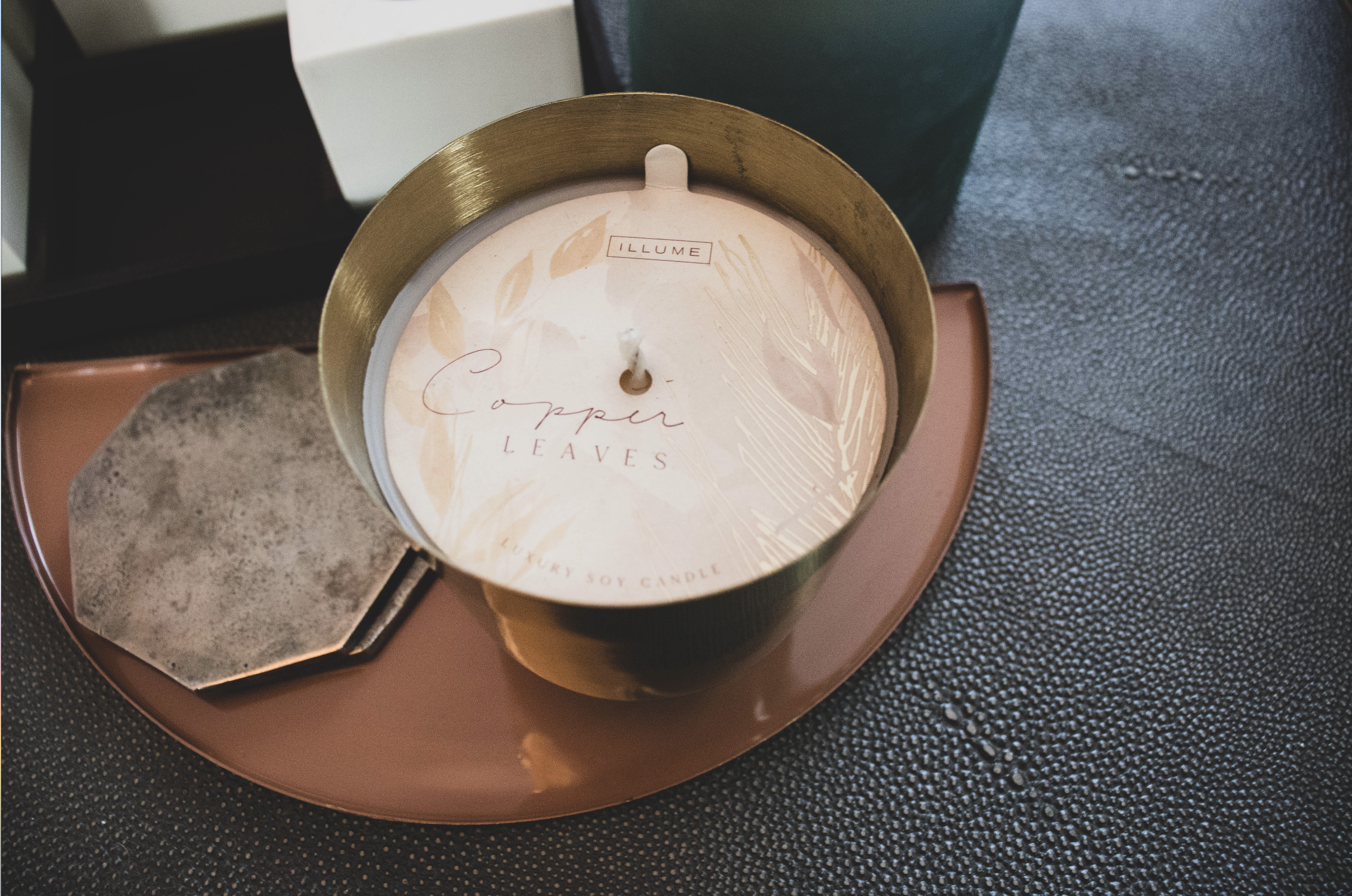 Copper Leaves Candle: One of the best fall scented candles of 2020. The candle is on a leather-topped coffee table next to a black and white block tic-tac-toe.