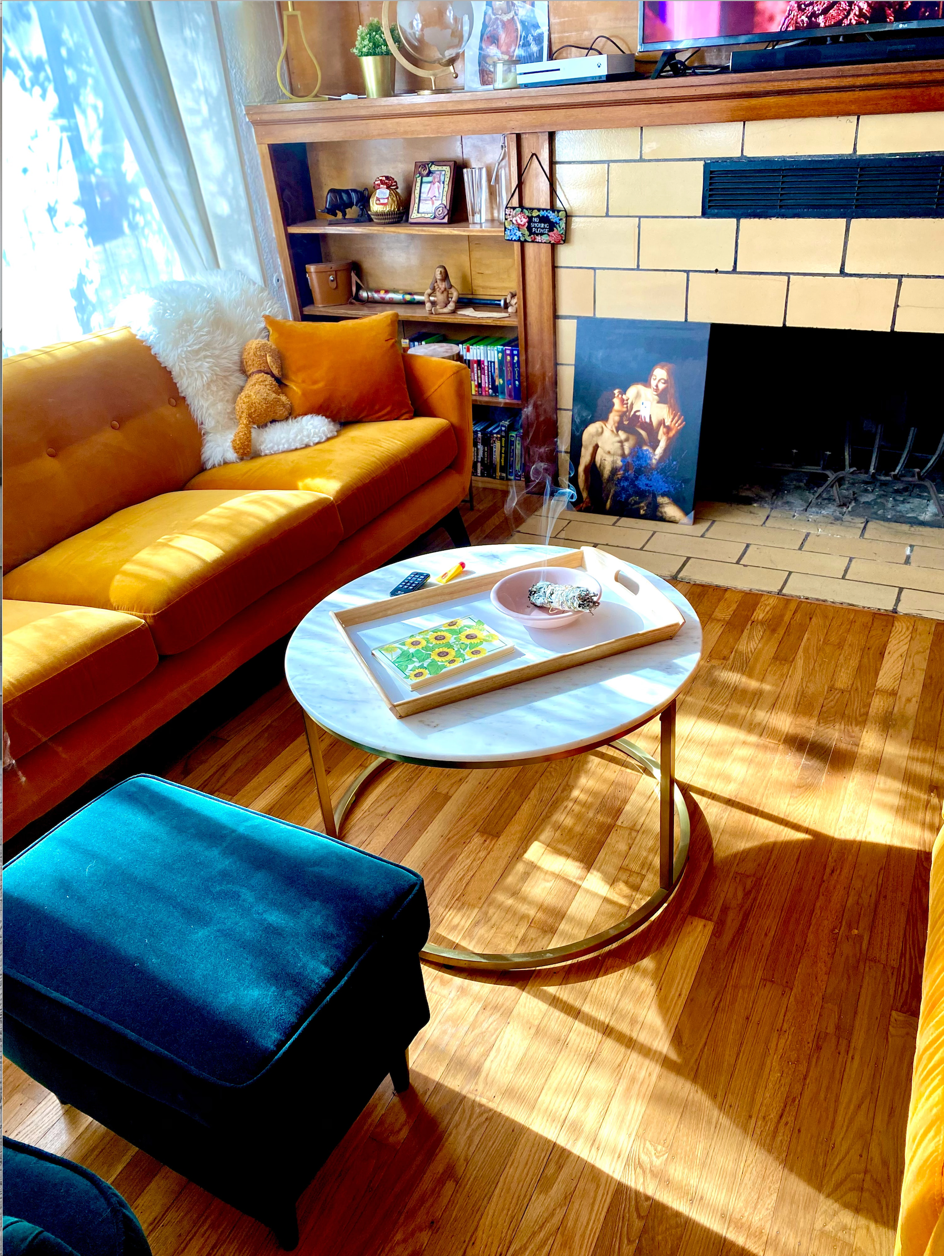 A colorful living room with a coffee table decor that includes a dining tray with a book and bowl for burning incense