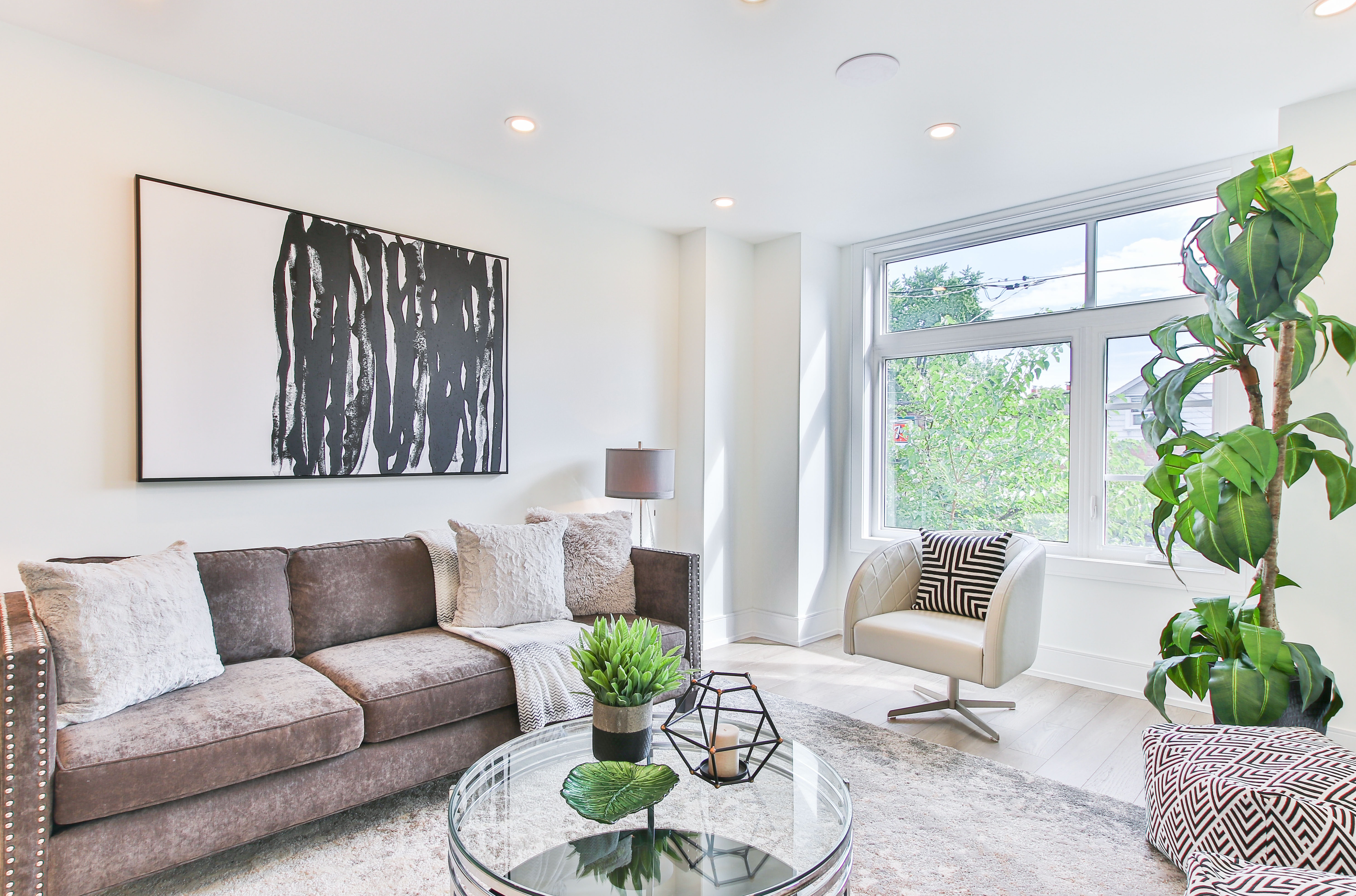 A living room view from the entrance. You can see a 3-seat couch with beautiful black and white artwork above it, a white accent chair in front of a huge window to the outdoors, a lovely plant in the forefront, and a glass coffee table to allow for light to bounce around the room unobstructed