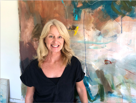 Jennifer McHugh standing in front of one of her abstract art pieces. She is in her studio.