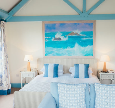 A coastal-inspired bedroom interior design with coastal blue accents, an ocean painting above the bed, and even a custom blue wooden lattice to highlight the peaked ceiling
