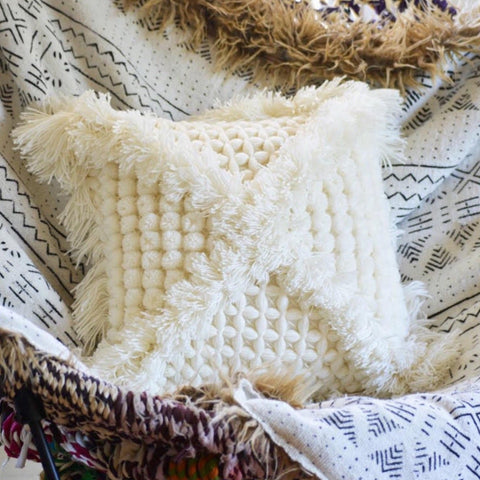 A cream cushion with woven accents