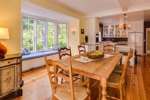 A farmhouse kitchen with a large wooden table and chairs, a maroon wall behind the cabinets, and white cabinetry