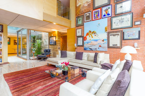 An art deco-inspired living room using lots of colors, an orange accent wall with photos, art, and colorful frames on a large gallery wall, a colorful rug