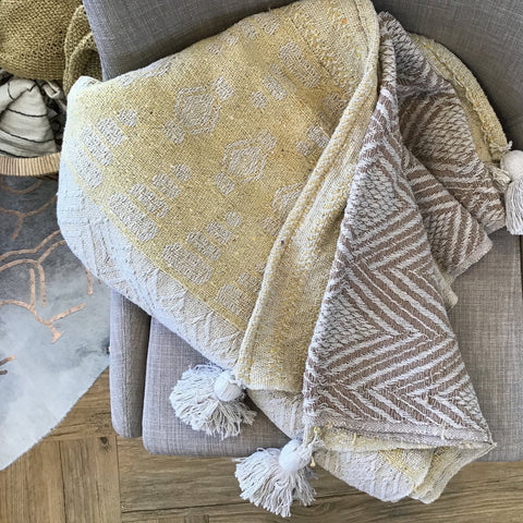 A mustard and tan woven throw on a gray chair to add texture and warmth
