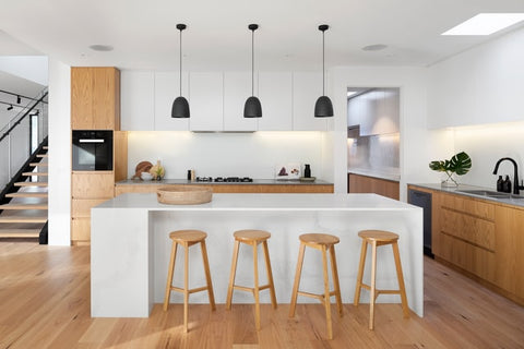 A modern kitchen in a Scandanavian style. This kitchen has white on the island and uppers, offset by natural wood-tone cabinets on the bottom.
