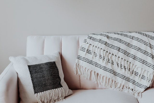 The right side of a light pink couch with a black and white fringed pillow and gray and white striped throw blanket on the back