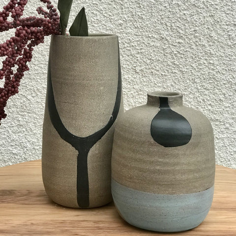 Two terra cotta hand-painted vases in neutral colors of gray, black and a light blue accent