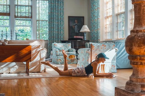 A traditional living room with multiple patterns in blues working together, classic wood furniture, and a woman laying on the floor in the foreground reading