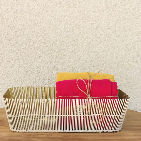 White and brass wire basket with napkins in it to illustrate a storage use