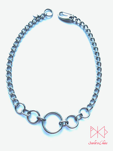 Stainless steel Luna Phase chain choker with multiple o rings in reducing sizes indicating a moon phase pattern. Shown flat with new links