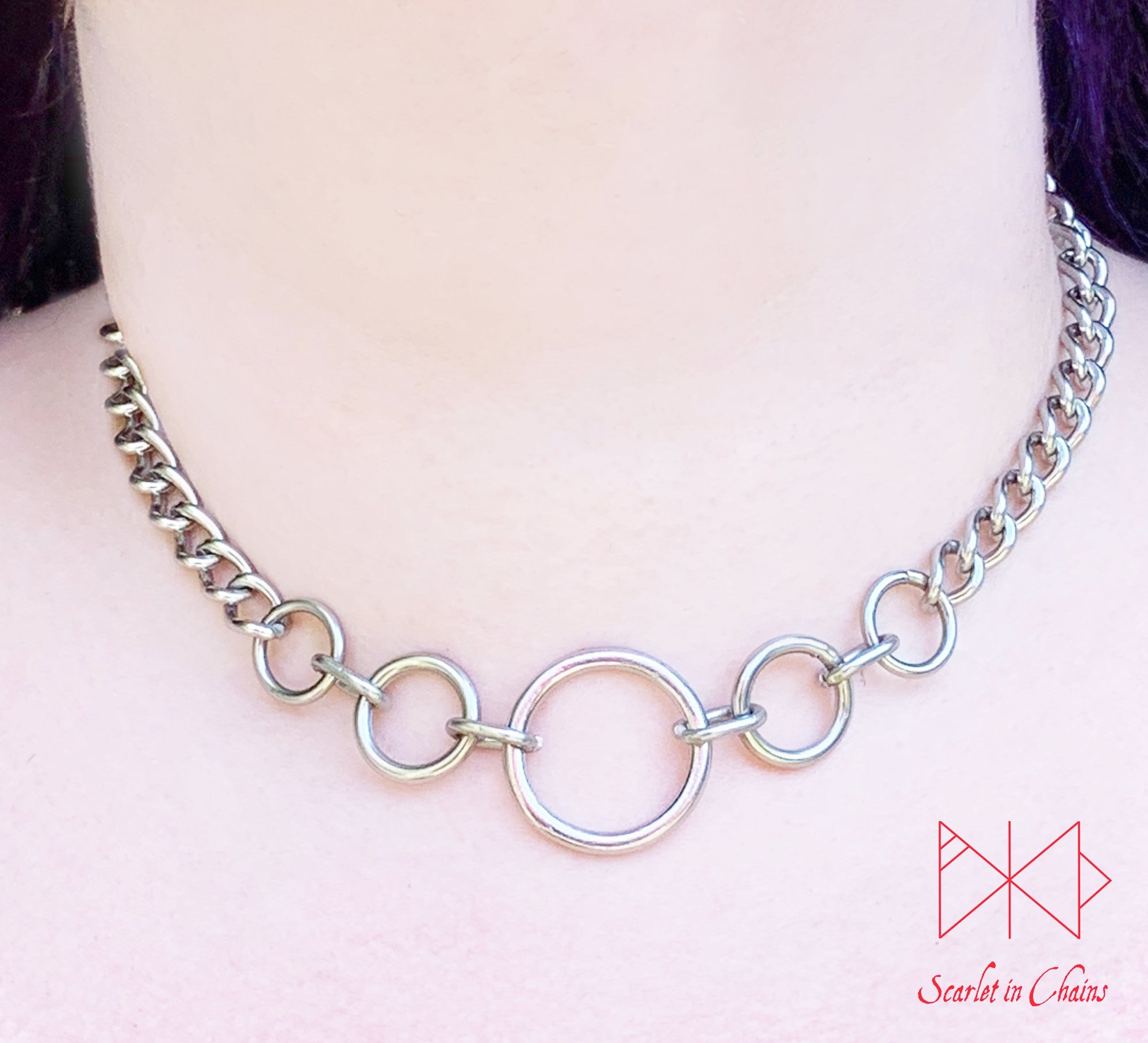 Stainless steel Luna Phase chain choker with multiple o rings in reducing sizes indicating a moon phase pattern. Shown worn with new links