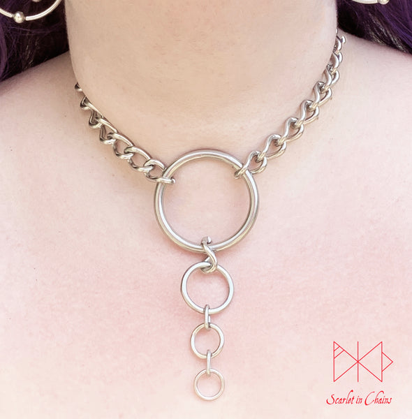 Alignment choker worn Stainless steel chain collar with central O ring with 3 smaller o rings cascading in size suspended from it shown with new links