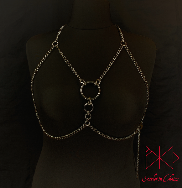 mannequin shot of Alignment body harness worn, a halternect stainless steel chain harness. with triangular chains over the chest bikini top style. with 3 depending in size, Stainless Steel O rings. fasted with a stainless steel clasp at the waistband