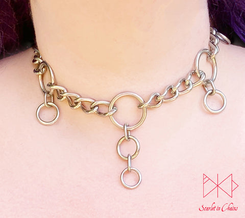 Worn image of Coven collar, 3mm stainless steel chain collar with 5 O rings set within the chain to represent the 5 points of the pentagram. hanging from the 4 side rings is 1 smaller O ring hanging off the central O ring is 2 smaller rings with new links