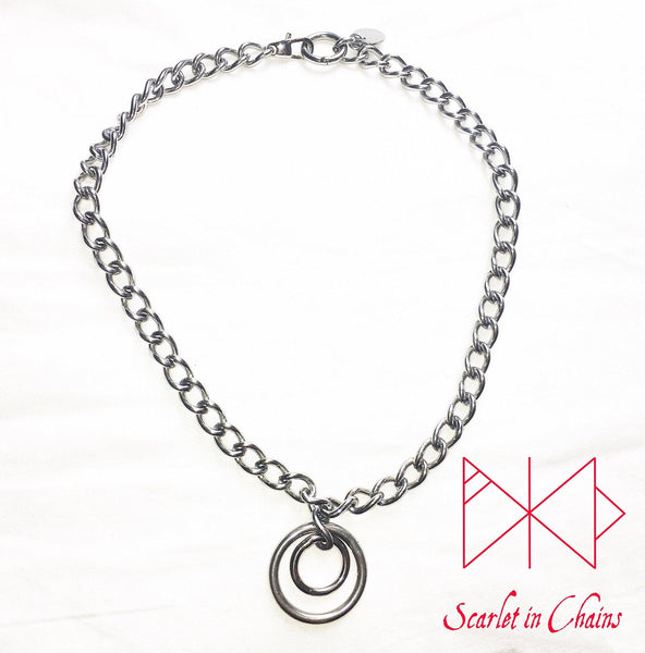 Stainless steel chain choker with a double stainless steel O ring pendant which consists of a smaller o ring inside a larger one.  finished with a stainless steel clap flat shot