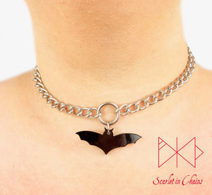 Bat choker worn by model. Stainless steel chain choker with stainless steel o ring at its centre with a black perspex bat pendant hung from the O ring