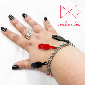 Worn shot of spanking paddle bracelet, stainless steel chain bracelet with perspex spanking paddle charms shown in black and red