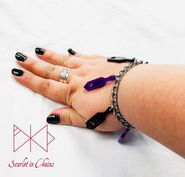 worn shot of spanking paddle bracelet, stainless steel chain bracelet with purple and black perspex spanking paddle charms
