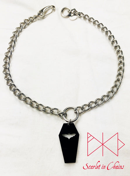 Coffin choker shown flat on a white background. Stainless Steel chain choker with stainless steel O ring at it centre. With a black perspex coffin pendant with a bat cut out suspended from the ring. At the back of the choker a strong easy to use stainless steel clip and an o ring to fasten it to. completed with a stainless steel hand stamped scarlet in chains logo tag