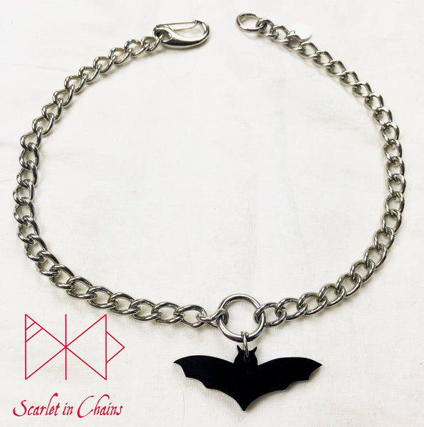 Bat choker flat on white background. Stainless steel chain choker with stainless steel o ring at its centre with a black perspex bat pendant hung from the O ring. Finished with our easy to use stainless steel clasp and hand stamped stainless steel logo tag.