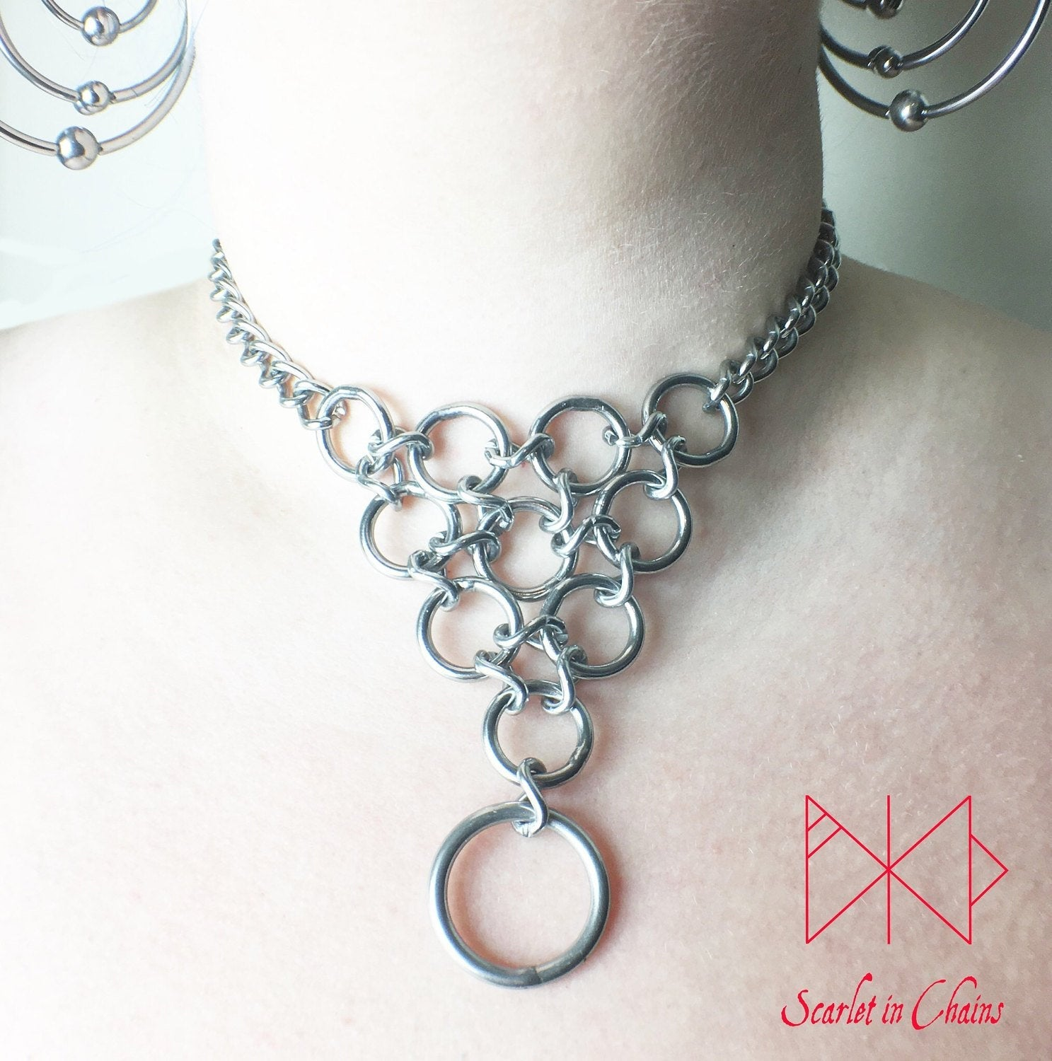 Huntress Day Collar worn Stainless steel chain choker with a triangle of o rings and a larger o ring hanging from the point of the inverted triangle of rings