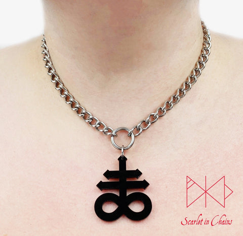 Leviathan cross choker worn by model. Stainless steel chain choker with stainless steel O ring at centre. Suspended from the O ring is a black perspex Leviathan cross charm.