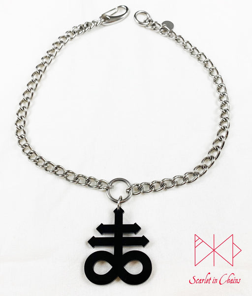 flat shot of Leviathan cross choker on white background. Stainless steel chain choker with stainless steel O ring at centre. Suspended from the O ring is a black perspex Leviathan cross charm. with an easy to use stainless steel clasp and an o ring to close the choker, finished with a hand stamped scarlet in chains logo tag.