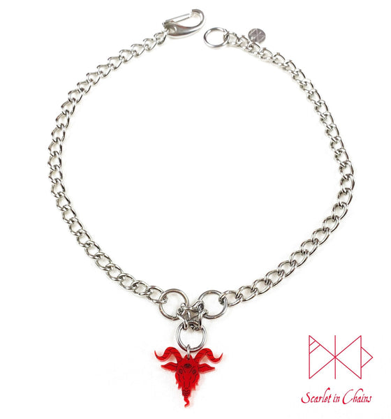 Baphomet choker necklace. A stainless steel chain choker necklace with 3 stainless steel O rings forming an inverted triangle. Hanging from the inverted triangle of O rings is a red perspex Baphomet pendant with hand finished black facial details. Necklace is closed with an easy to us stainless steel clasp. Shown flat on a white background