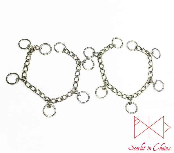 flat shot of mini valkyrie cuffs. stainless steel chain cuffs with 5 o rings suspended from them show with padlock finish