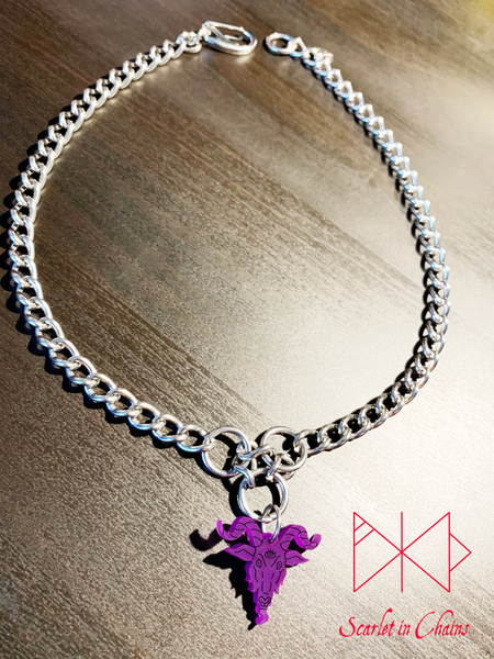 Baphomet choker necklace in purple. A stainless steel chain choker necklace with 3 stainless steel O rings forming an inverted triangle. Hanging from the inverted triangle of O rings is a purple perspex Baphomet pendant with hand finished black facial details. Necklace is closed with an easy to us stainless steel clasp. Shown flat   Edit alt text