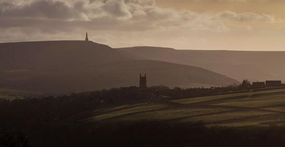 Stoodley Pike monument and Heptonstall Church, silhouetted by late afternoon sunshine