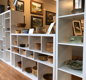 Shelves of pottery and wood turnings and paintings on wall