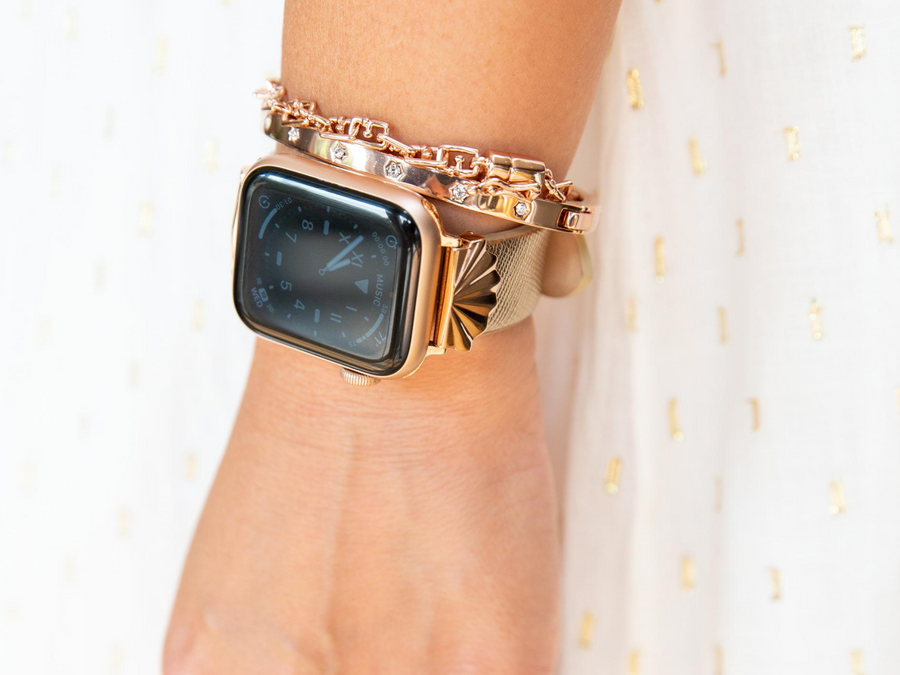 Woman arm by her side, with Goldenerre rose gold apple watch, rose gold rhinestone bracelet, and rose gold g-link bracelet. Woman is wearing white and gold dress.