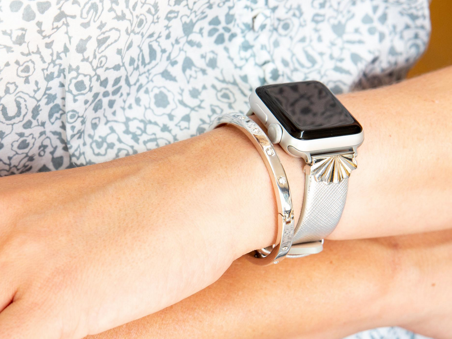 Shiny silver starburst on a silver saffiano leather band, shown with two stacked rose gold bracelets - a g-link bracelet and rhinestone bracelet, against a white and gold dress shown on a silver apple watch and with a silver rhinestone bracelet. Woman has arms crossed and wearing an white and blue dress