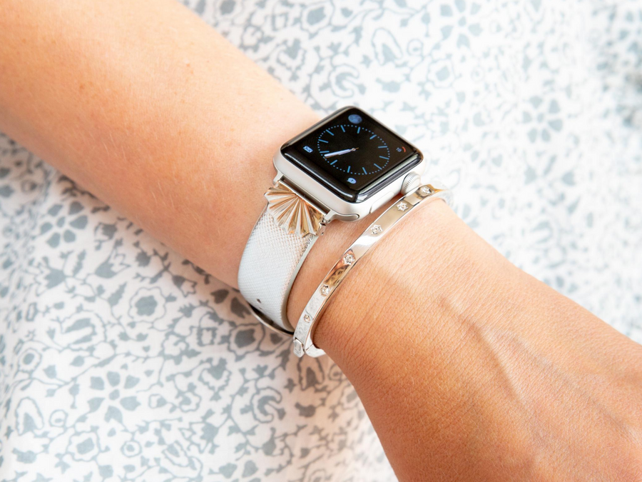 Shiny silver starburst on a silver saffiano leather band, shown on a silver Apple Watch, with a silver rhinestone bracelet. Woman is wearing a white and blue dress.