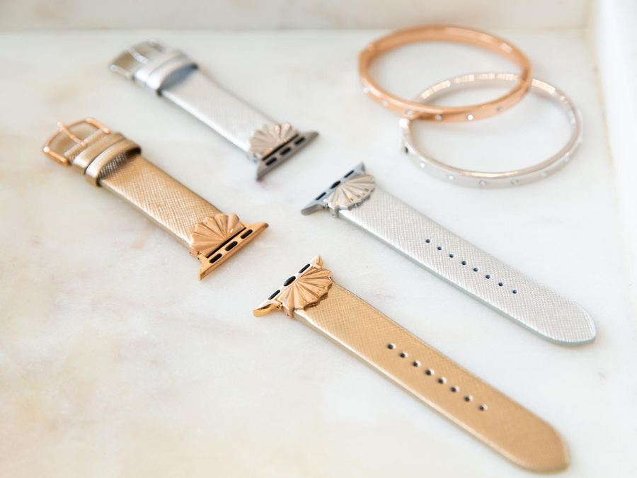 Laydown of Goldenerre gold and silver starburst bands, shown without the Apple Watch, next to a rose gold and silver rhinestone bracelet, shown on a marble tray