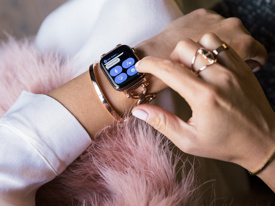 Woman writing a test message on her rose gold Apple Watch, wearing Goldenerre rose gold classic link watch band, rose gold bangle, and rose gold rings