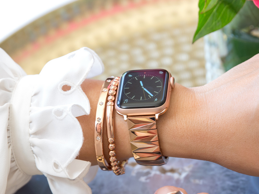 Stunning rose gold women's band for the Apple Watch, made of gleaming rose gold pyramids. Shown here on a Gold Aluminum Apple Watch Series 5, rose gold beaded bracelet and rose gold rhinestone bracelet.  The modern arm party featuring the Apple Watch is femininely styled with a white blouse and shown with a gold tray in the background.