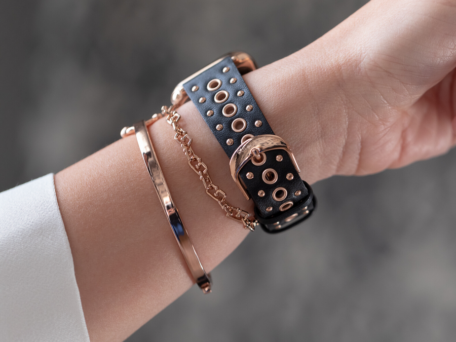 Rose gold buckle on the underside of wrist of woman wearing Goldenerre black leather band for the Apple Watch, embellished with rose gold grommets. Accessorized with rose gold g-link bracelet and rose gold classic link bracelet for a modern arm party with the Apple Watch
